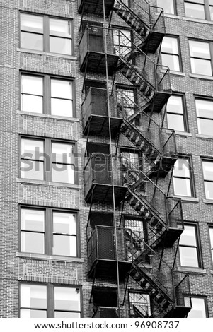 Exterior fire escape stairs on the outside of an old brick building in black and white.