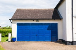Exterior of a double garage with a blue metal up and over door attached to a house. Hertfordshire. UK.
