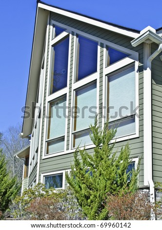 Exterior of a home with the shades down on some of the windows to reduce sun exposure or give privacy.