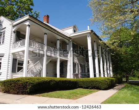 exterior of a large home with a front porch with columns and a balcony