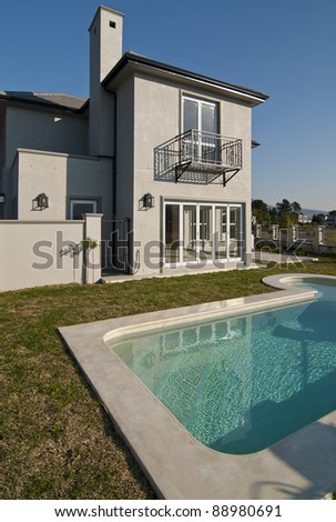 Exterior of a luxury house with a swimming pool on a sunny day