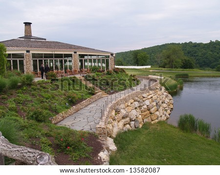 exterior of a modern building by a golf course and calm water
