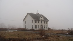 Exterior of an abandoned and neglected house in the middle of nowhere. Seasonal.