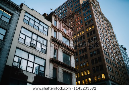Exterior of modern constructed real estate with lights in office windows located in downtown, tall buildings with rental apartments for residents and commercial property for corporation and companies #1145233592