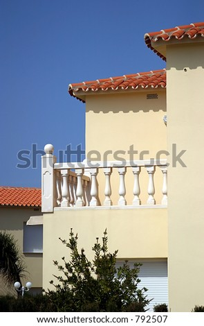 Exterior of modern new house with terrace and sunny blue sky in Spain
