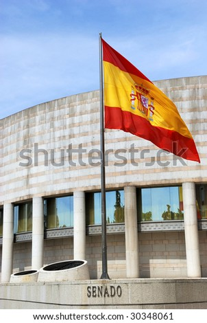 Exterior of the building of the Senate (Senado) in Madrid, Spain, Europe. At the forground the the Spanish flag.