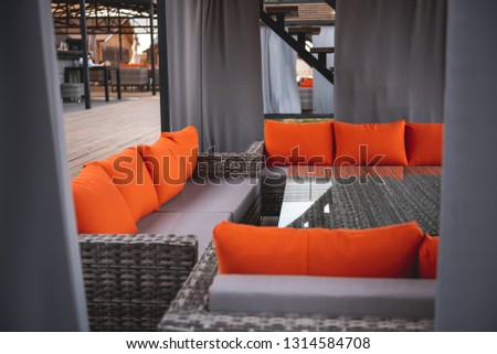 Exterior of the lovely patio designed in grey color with bright orange pillows on the couches and glass table in the middle