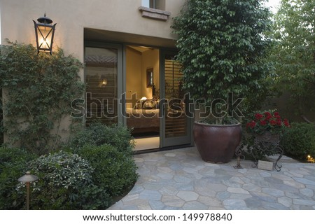 Exterior shot with crazy paving and plants with view into bedroom #149978840