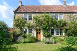 Exterior View and Garden Lawn of a Beautiful Old Rural English Cottage House