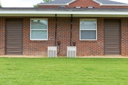Exterior view of a generic apartment building with older model HVAC heat pumps, twin windows, green grassy lawn, creative copy space, horizontal aspect