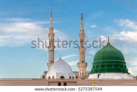 Exterior view of minarets and green dome of a mosque taken off the compound.