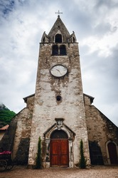 Exterior view of the Eglise du Cloitre, ancient medieval gothic church near the castle of Aigle, small winemaking village in the Vaud region of the swiss alps, switzerland. Detail of the bell tower