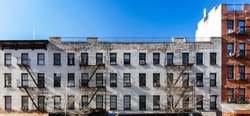 Exterior view of the facade of an old brick apartment buildings with windows and fire escapes in New York City NYC