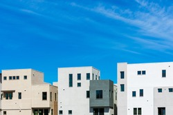 Exterior view of typical new multifamily low-rise residential row building under beautiful blue sky.