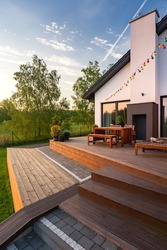 Exterior view of villa with patio with wooden flooring, furniture and steps