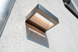 Exterior wall light on renovated plaster structure in outdoor courtyard