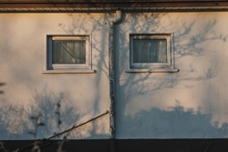Exterior wall of a building illuminated in sunset orange colour and shapes of tree shadows. two windows with downpipe creating an illusion of a human face - eyes and nose.