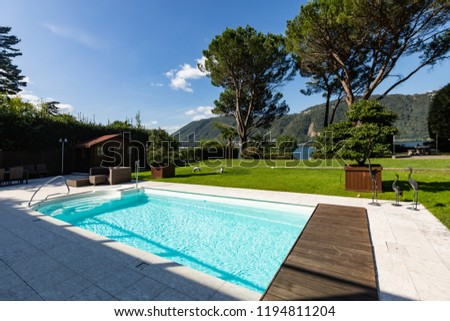 Exterior with swimming pool, garden and lake view. Nobody inside
