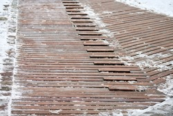 Exterior wooden decking covered with snow. Wooden ramp on playground with non-slip crossbeams, used to ascend up inclined plane.