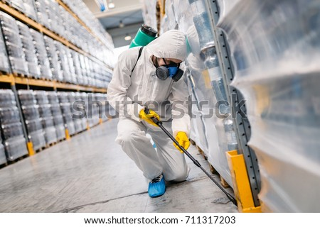 Exterminator in bottling plant spraying pesticide with sprayer.