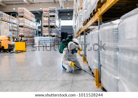 Exterminator in industrial plant spraying pesticide with sprayer.  #1011528244