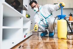 Exterminator in work wear spraying pesticide with sprayer. Selective focus.