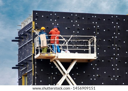 External facade thermal insulation. Professional construction workers on scissor lift insulating wall facade with mineral wool for thermal protection. Workers wearing safety harness insulated wall