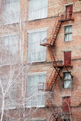 External fire escape staircase on an old brick building of factory, plant. Big windows, white birch trees grows near