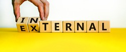 External or internal symbol. Male hand flips wooden cubes and changes the word 'external' to 'internal'. Beautiful yellow table, white background, copy space. Business concept.