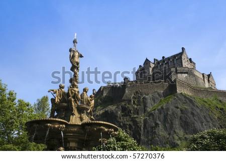 extinct volcano castle rock rising above the ross fountain in princes street gardens in edinburgh scotland