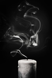 extinct white candle with smoke on a black background, black and white photo.