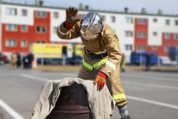 Extinguishing a major fire. A professional fireman in a special suit extinguishes an open fire with. Regional fire-fighting exercise in the training area with urban and contract firefighters.
