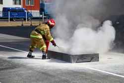 Extinguishing a major fire. A professional fireman in a special suit extinguishes an open fire with a fire extinguisher. Training firefighters for extinguishing fires
