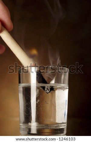 extinguishing an ear candle in a glass of water