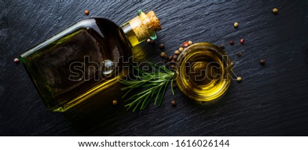 Extra virgin olive oil in a glass bottle, flavored with rosemary and peppercorns on black stone slate Stock photo ©