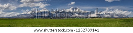Extra wide panorama of High Tatra mountains during April with snowy hills,  blue sky with fluffy clouds, Vysoke Tatry, Slovakia Stockfoto ©