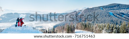 Extra wide panorama of the Carpathians mountains landscape, forests in a white haze, ski slopes, winter ski resort Bukovel. Two snowboarders enjoying, resting on top of the mountain on a sunny day