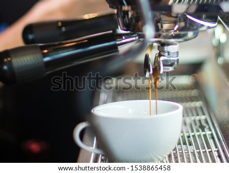 Extracting espresso from an espresso machine into a white cup. #1538865458