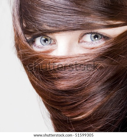 extrange look of a young woman with blue eyes with her hair around the eyes
