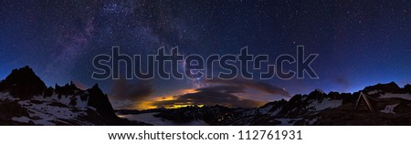 Extraordinary 360 degree panorama of the night sky in the Swiss alps at 2700+ meters. Visible is a glow from a city and the majestic milky way above it
