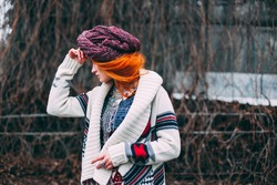 Extravagant beautiful young woman with red hair in a turban in party-colored dress style of ethnic and boho with elegant patterns on her face posing in winter cold park thinking