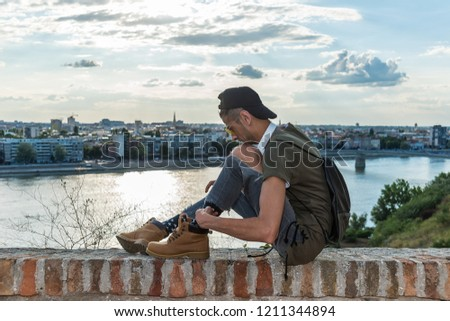 Extravagant (hipster) male model with sunglasses, headphones and a black hat. In the background is the river Danube and the city of Novi Sad #1211344894