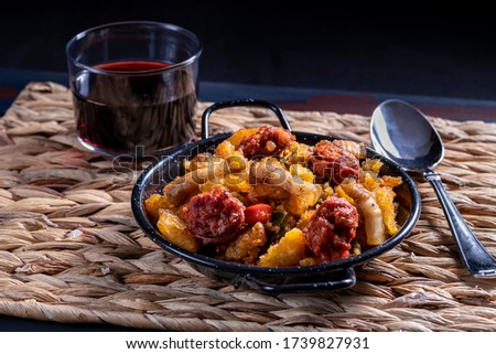 Extremadura crumbs, a typical Spanish dish from Extremadura, breadcrumbs, bacon, red and green peppers, garlic and paprika, with a glass of red wine on an esparto tablecloth