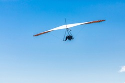 Extremal air sports competition - Hang gliding. Overhead view of the soaring hang gliding pilot against the clear blue sky