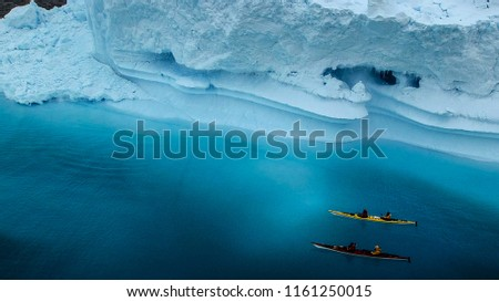extreme adventure sport, Antarctica kayaking, paddling on kayak between antarctic icebergs, winter leisure outdoors activity