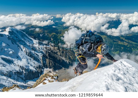 Extreme alpinist in high altitude on Aiguille de Bionnassay mountain summit, Mont Blanc massif, Alps, France