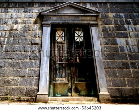 Extreme angle looking up. Old Gothic door weather,worn stained, abandon, bolted and chained closed. Set in a stone wall, with Greek revival type frame,
