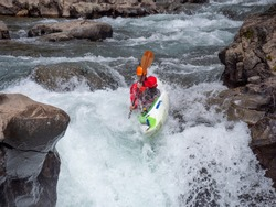 Extreme athlete whitewater kayaking over a waterfall on the McCloud River in northern California