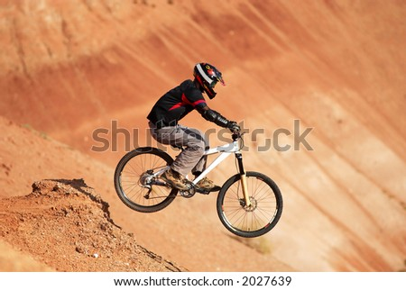 Extreme biker in red canyon - stock photo