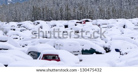 Extreme blizzard weather conditions bring heavy snow that buries hundreds of vehicles in car park or scrap junk yard.